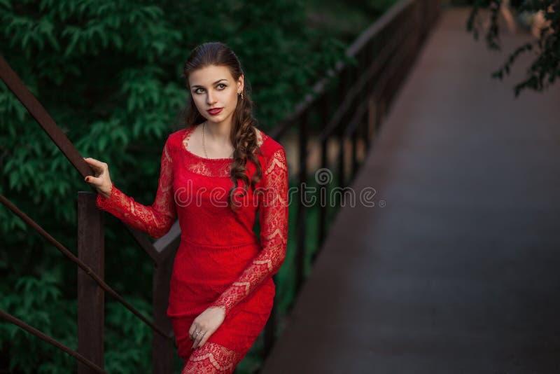 Het mooie maniervrouw stellen in rode kleding met creatief kapsel In stedelijk portret op groene achtergrond stock afbeeldingen