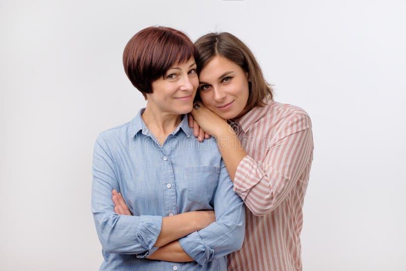 Het mooie matureseniormamma en haar volwassen dochter koesteren, bekijken camera en glimlachen royalty-vrije stock afbeelding