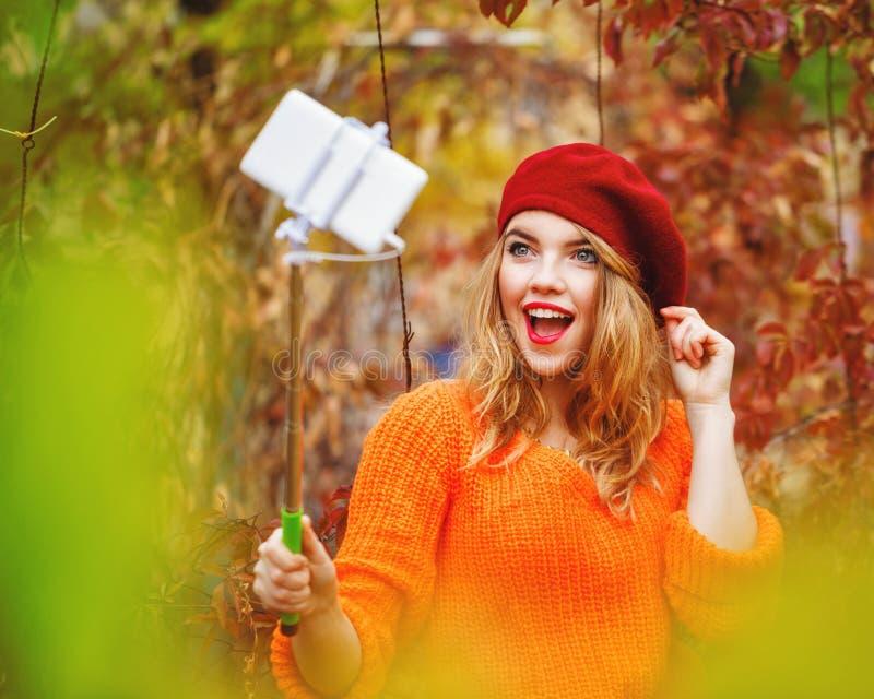 Het mooie meisje in baret en sweater doet zelf-portret op telefoon stock foto