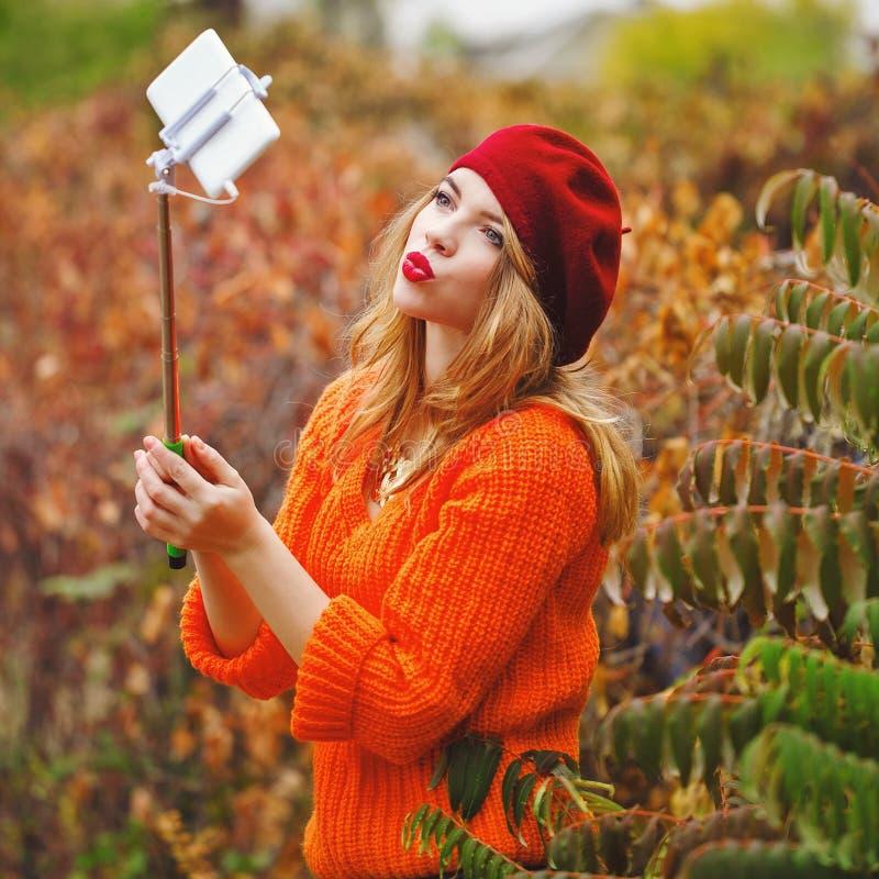 Het mooie meisje in baret en sweater doet zelf-portret op telefoon royalty-vrije stock foto