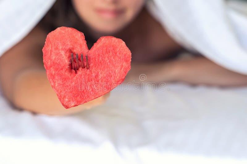 Het mooie meisje in bed geeft hart van watermeloen op een vork royalty-vrije stock afbeelding