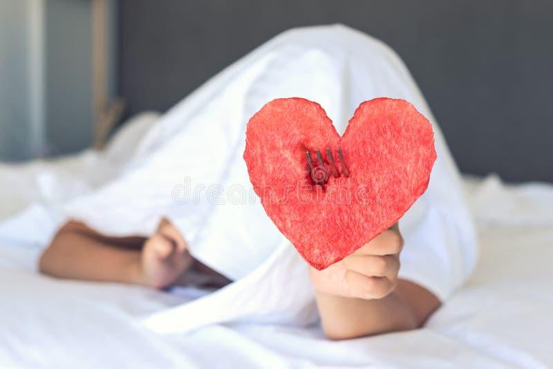 Het mooie meisje in bed geeft hart van watermeloen op een vork royalty-vrije stock foto's
