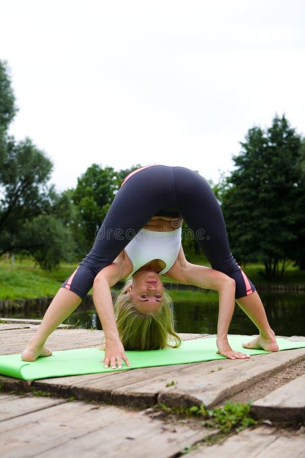 Het mooie meisje bevindt zich in een yoga stelt in het park royalty-vrije stock foto's