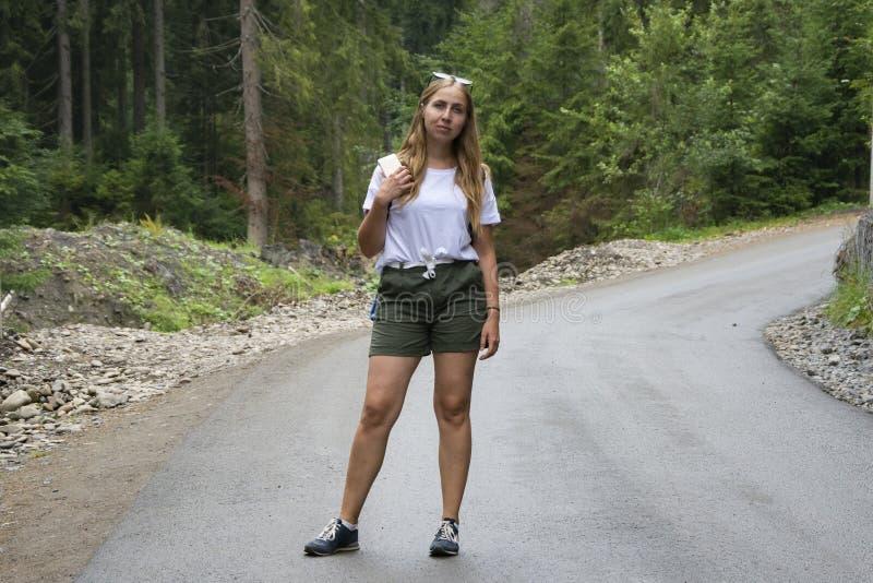 Het mooie meisje bevindt zich in het midden van een bergweg royalty-vrije stock foto's