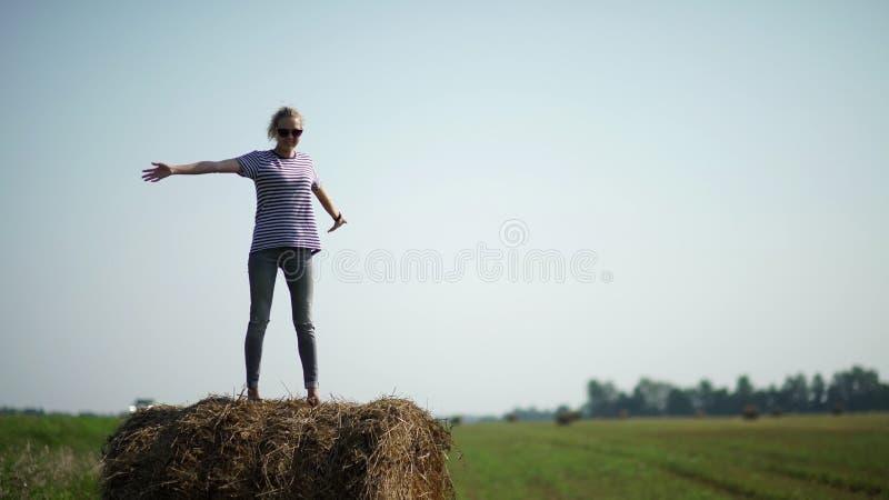 Het mooie meisje bevindt zich op hooibergen stock fotografie