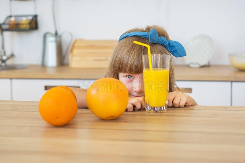 Het mooie meisje in blauwe kleding zit achter twee sinaasappelen bij de lijst royalty-vrije stock afbeeldingen