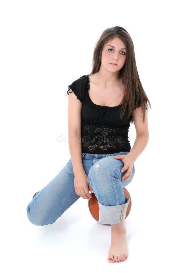 Het mooie Meisje dat van de Tiener in Jeans op de Bal van de Mand over Wit zit royalty-vrije stock afbeelding