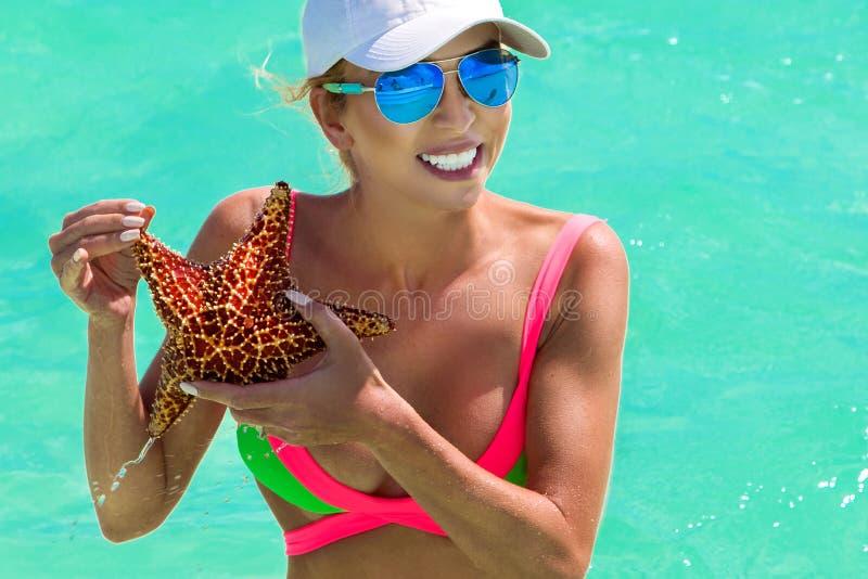 Het mooie meisje in de Caraïbische Zee, houdt in de handen van een zeester royalty-vrije stock fotografie