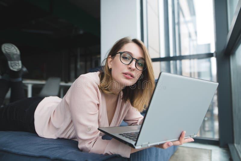 Het mooie meisje in de glazen ligt bij het venster op de bank met laptop in haar handen en bekijkt de camera royalty-vrije stock afbeelding