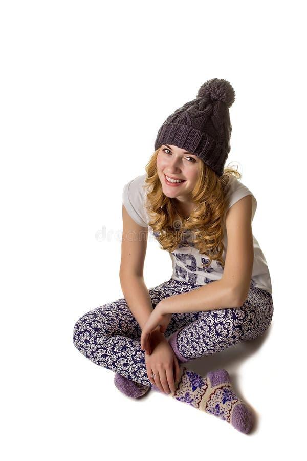Het mooie meisje in de winterhoed zit op een vloer royalty-vrije stock fotografie
