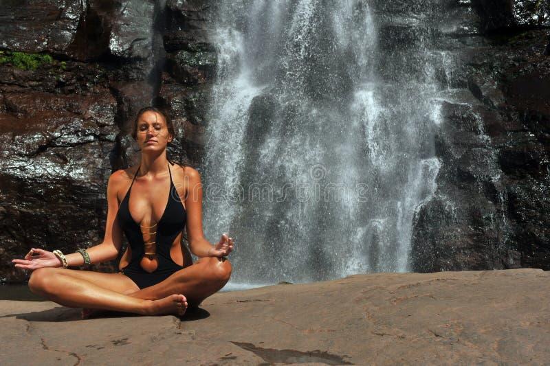 Het mooie meisje die zwart ééndelig zwempak dragen die in lotusbloemyoga mediteren stelt stock foto