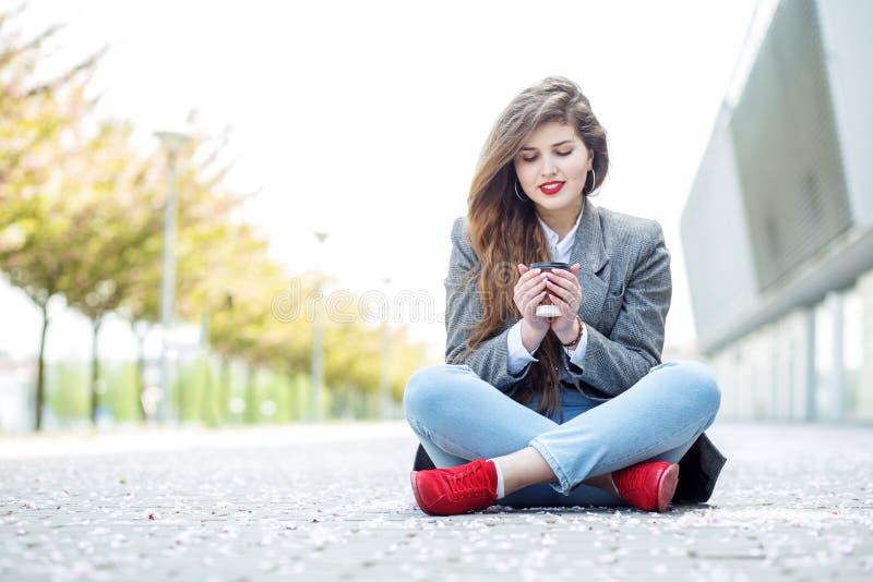 Het mooie meisje drinkt hete koffie Stedelijk concept levensstijl, vrije tijd, studenten stock afbeeldingen