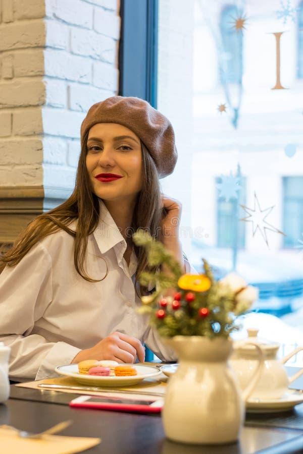 Het mooie meisje in een baret zit bij een lijst in een koffie met een kop en een cake en glimlacht stock afbeelding