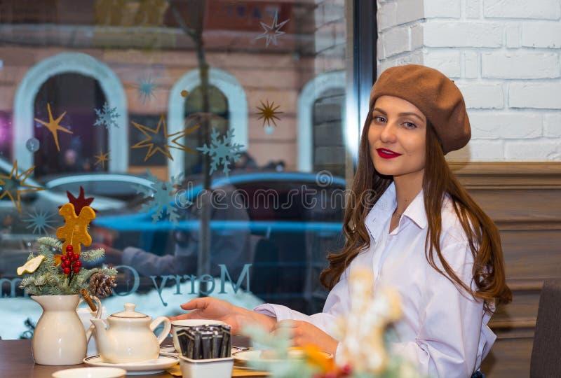 Het mooie meisje in een baret zit bij een lijst in een koffie met een kop thee royalty-vrije stock foto