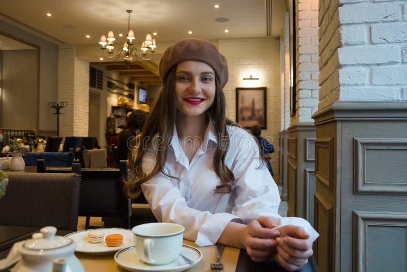 Het mooie meisje in een baret zit bij een lijst in een koffie met een kop thee en makarons royalty-vrije stock afbeelding