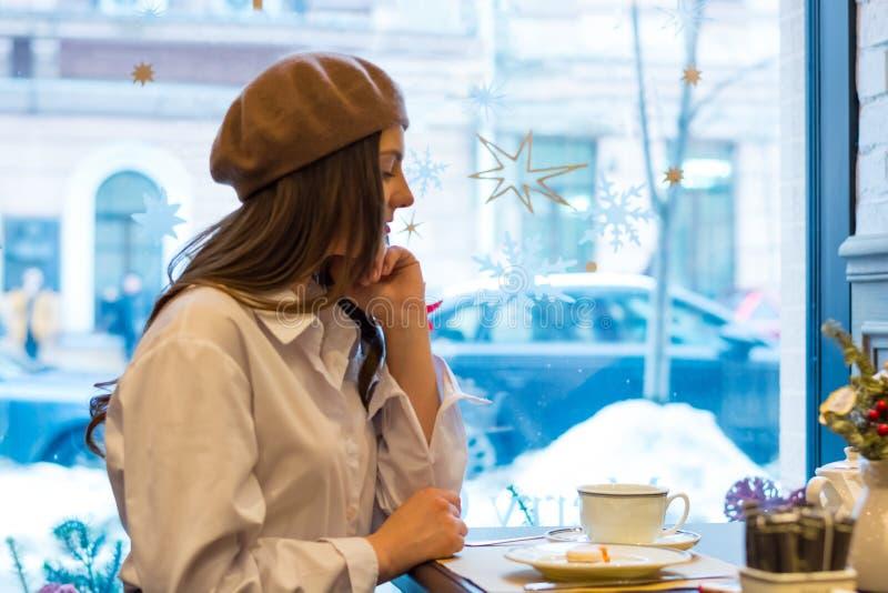 Het mooie meisje in een baret zit bij een lijst in een koffie met een kop thee, makarons stock afbeelding