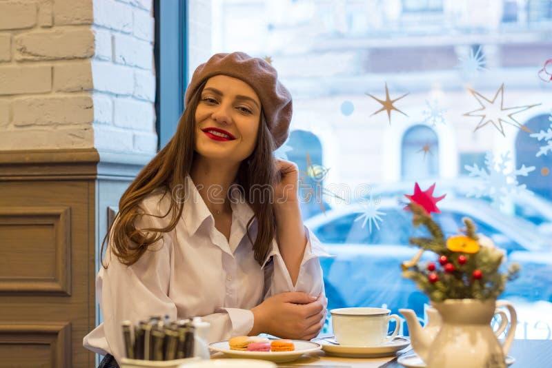 Het mooie meisje in een baret zit bij een lijst in een koffie met een kop thee, makarons royalty-vrije stock afbeeldingen