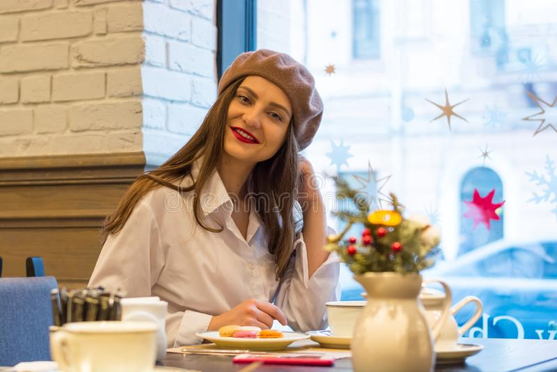Het mooie meisje in een baret zit bij een lijst in een koffie met een kop thee, makarons stock foto's