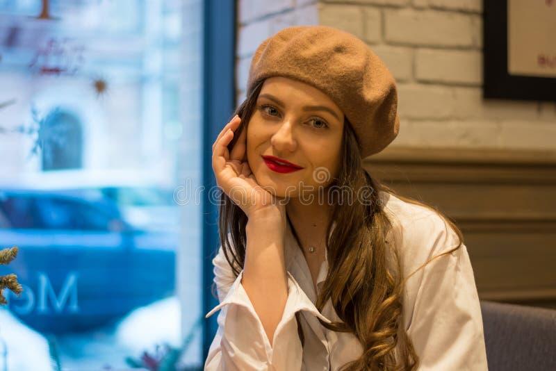 Het mooie meisje in een baret zit dichtbij het venster in een koffie royalty-vrije stock afbeelding