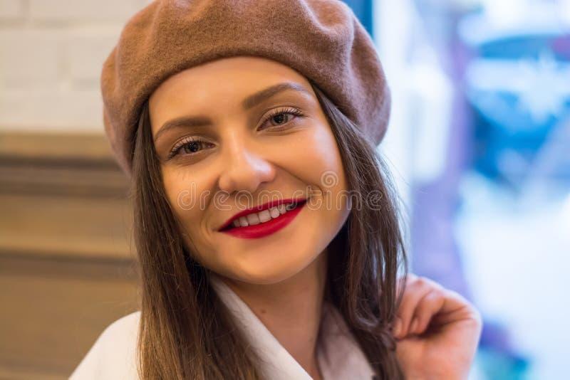 Het mooie meisje in een baret zit dichtbij het venster in een koffie stock foto