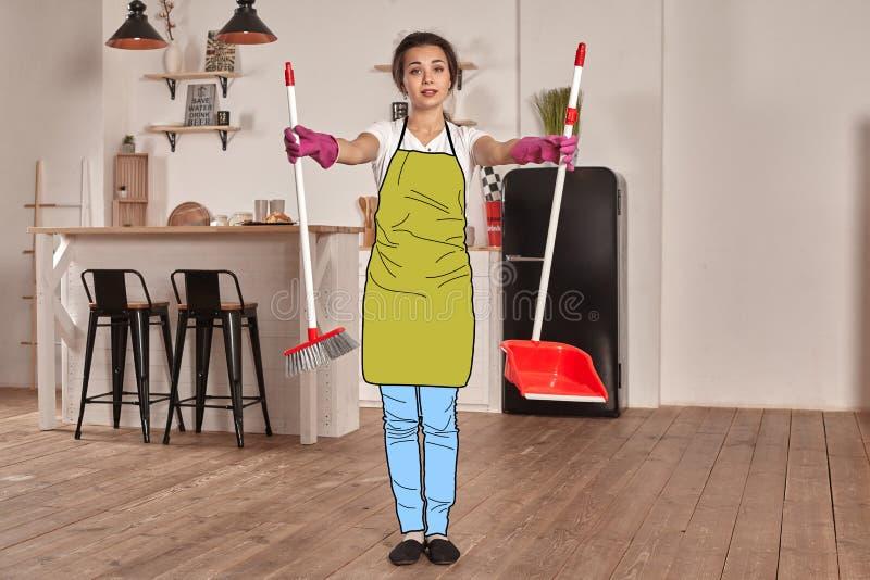 Het mooie meisje in een beeldverhaaljeans, een schort en rubberhandschoenen stelt tegen een keukenachtergrond met een borstel en  stock foto