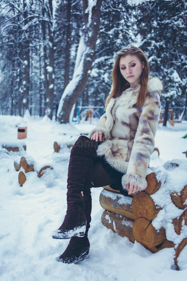 Het mooie meisje in een beige korte laag met stromend haar zit op een houten kader stock foto's