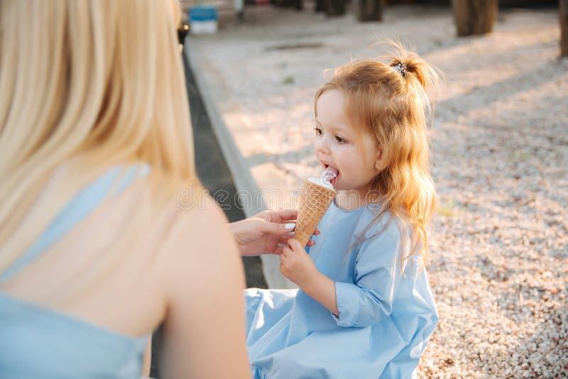 Het mooie meisje in een blauwe kleding die een roomijs, Mum eten helpt en veegt haar mond af stock afbeelding