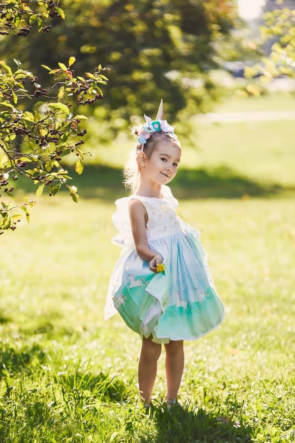 Het mooie meisje in een blauwe kleding in een groen tuinpark die zonnige dag glimlachen viert Halloween met eenhoorn royalty-vrije stock foto