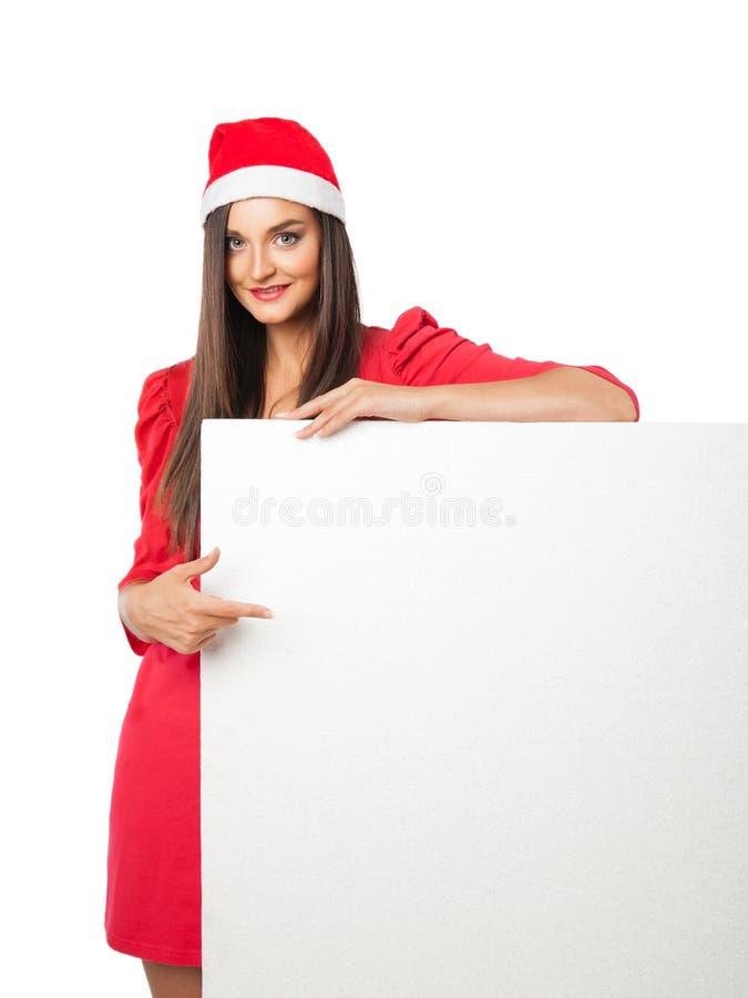 Het mooie meisje in een de helperhoed van de Kerstman houdt storaxschuim stock foto