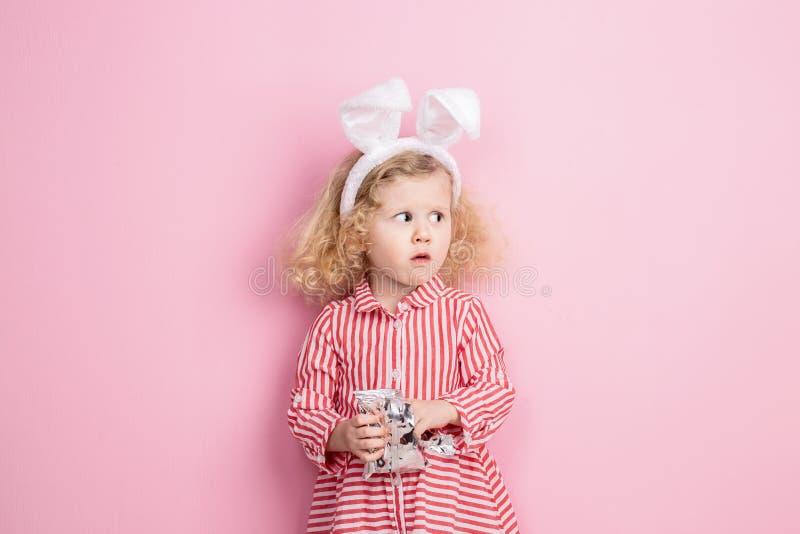 Het mooie meisje in een gestreepte rode en witte kleding en konijntjesoren op haar hoofd bevindt zich tegen een roze muur en stock foto's