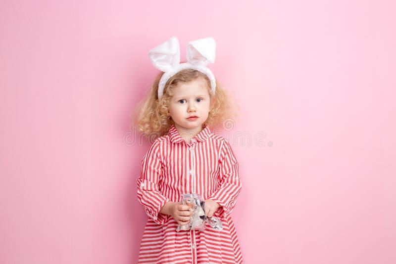 Het mooie meisje in een gestreepte rode en witte kleding en konijntjesoren op haar hoofd bevindt zich tegen een roze muur en royalty-vrije stock fotografie