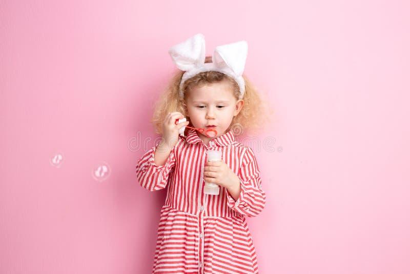 Het mooie meisje in een gestreepte rode en witte kleding en konijntjesoren op haar hoofd blaast zeepbels op die zich tegen a bevi stock fotografie