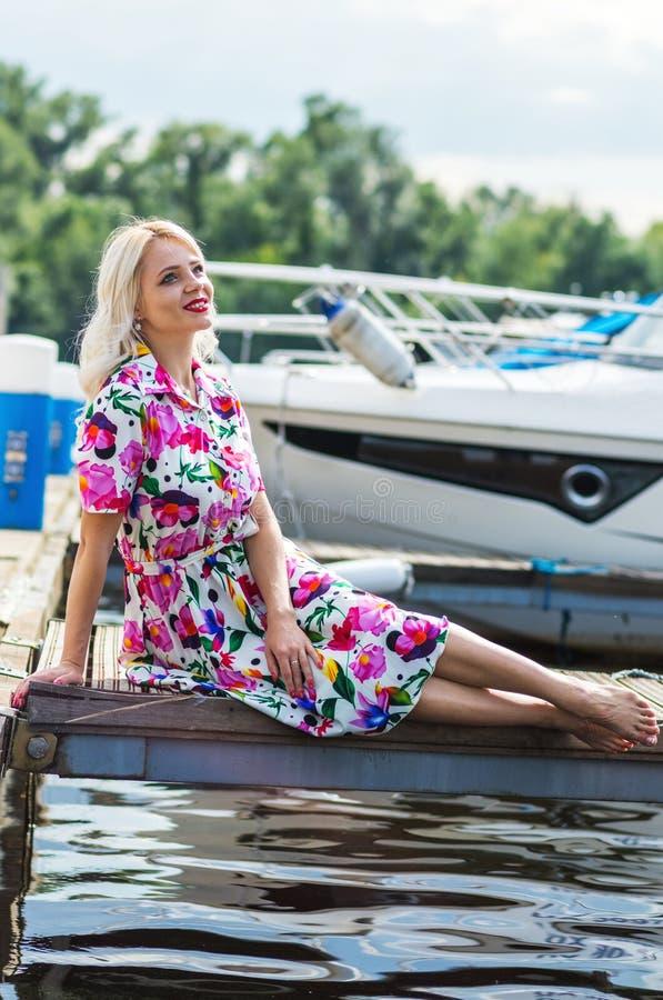 Het mooie meisje in een kleding zit op de pijler tegen de achtergrond van jachten in de zomer royalty-vrije stock foto