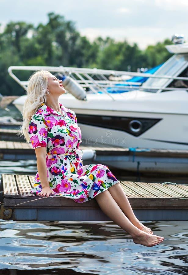 Het mooie meisje in een kleding zit op de pijler tegen de achtergrond van jachten in de zomer stock foto's