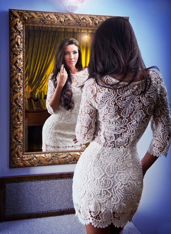 Het mooie meisje in een korte witte kleding die spiegel onderzoeken stock afbeeldingen