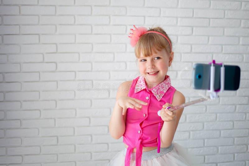 Het mooie meisje een kroon neemt een selfie op telefoon Het kind schiet video op het kanaal, jonge blogger stock afbeeldingen