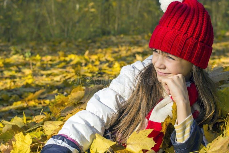Het mooie meisje in een rood GLB die in de herfst liggen verlaat en onderzoekt de afstand, het glimlachen stock afbeelding