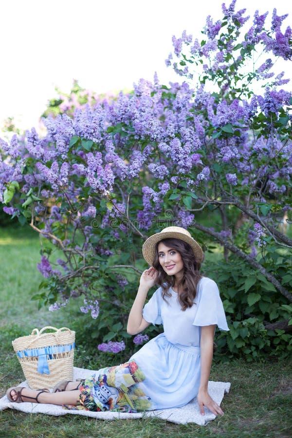 Het mooie meisje in een strohoed zit op een plaid en brengt gelukkig tijd aan een picknick in het park met een sering op de achte royalty-vrije stock afbeeldingen