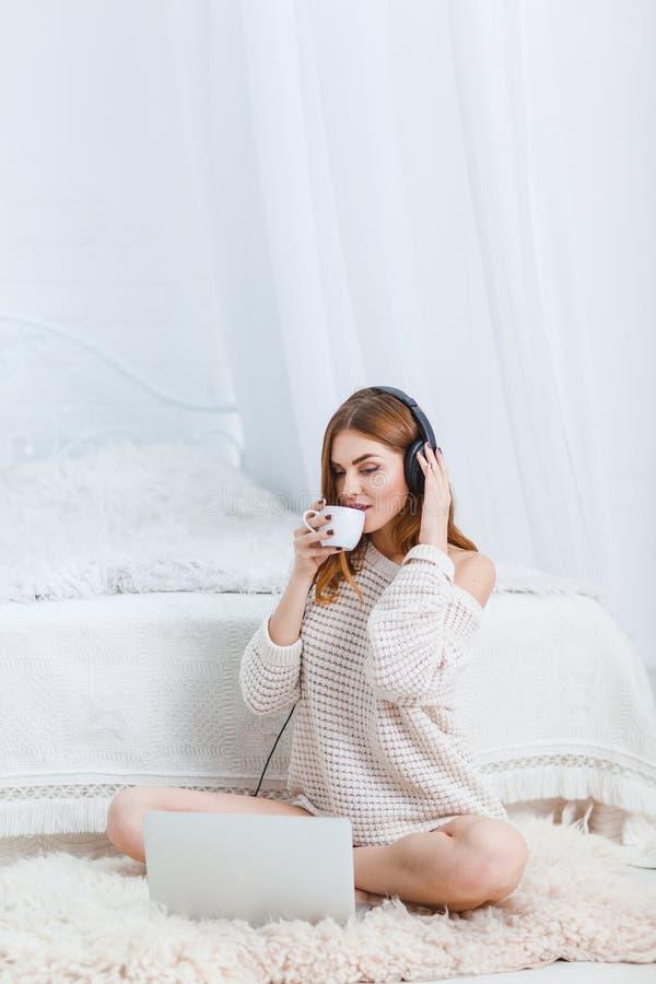 Het mooie meisje in een warme sweater, zit op de vloer dichtbij laptop met hoofdtelefoons, en drinkt thee binnen royalty-vrije stock afbeelding