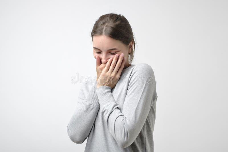 Het mooie meisje in eenvoudige pulover is schuw om een compliment te horen Zij verbergt haar gezicht stock foto's