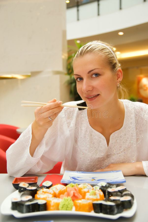 Het mooie meisje eet sushi stock foto's