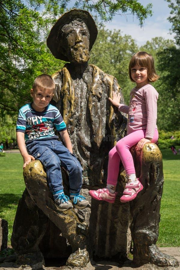 Het mooie meisje en de jongen zitten op het beeldhouwwerk van dichter en schilder in openbaar park in Novi Sad, Servië royalty-vrije stock fotografie