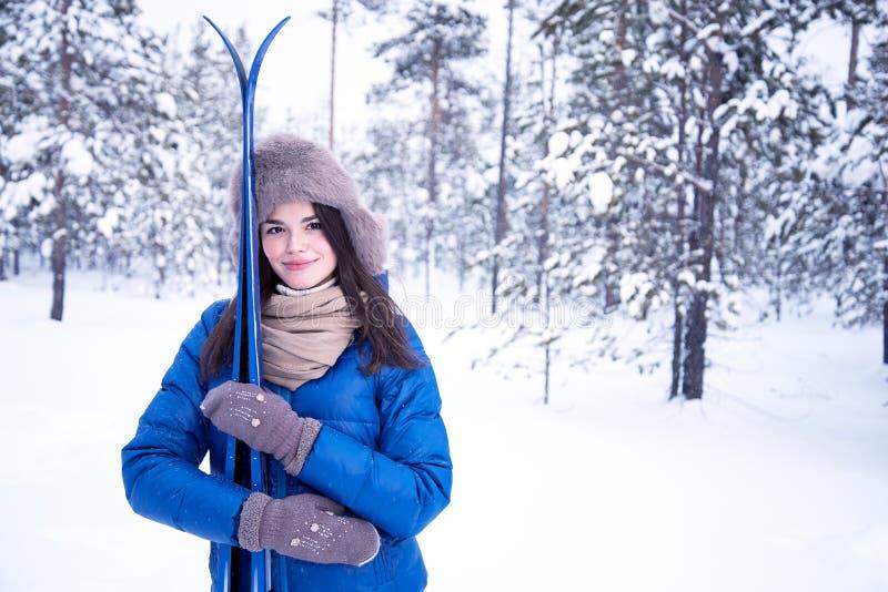 Het mooie meisje gaat ski?end in het hout stock foto