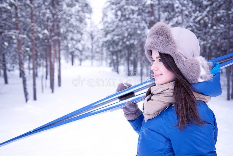 Het mooie meisje gaat ski?end in het hout royalty-vrije stock afbeeldingen