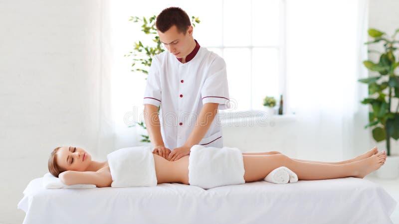 Het mooie meisje geniet massage en kuuroord van behandelingen stock afbeelding