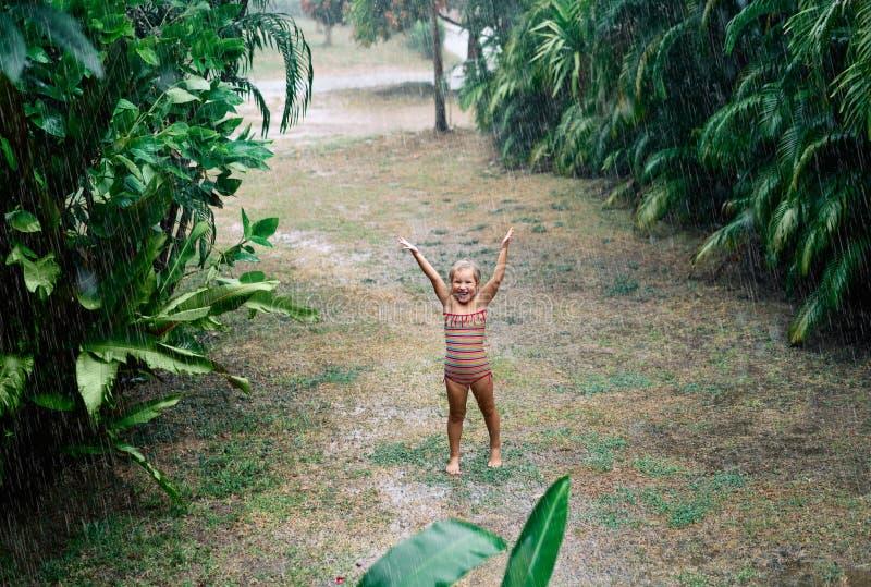 Het mooie meisje geniet van de regen en het dansen op de straat onder regenval in de zomer stock fotografie