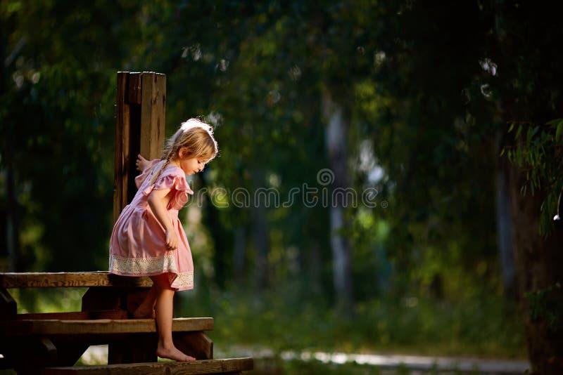 Het mooie meisje glimlacht terwijl status op de kleine houten hangende brug royalty-vrije stock foto