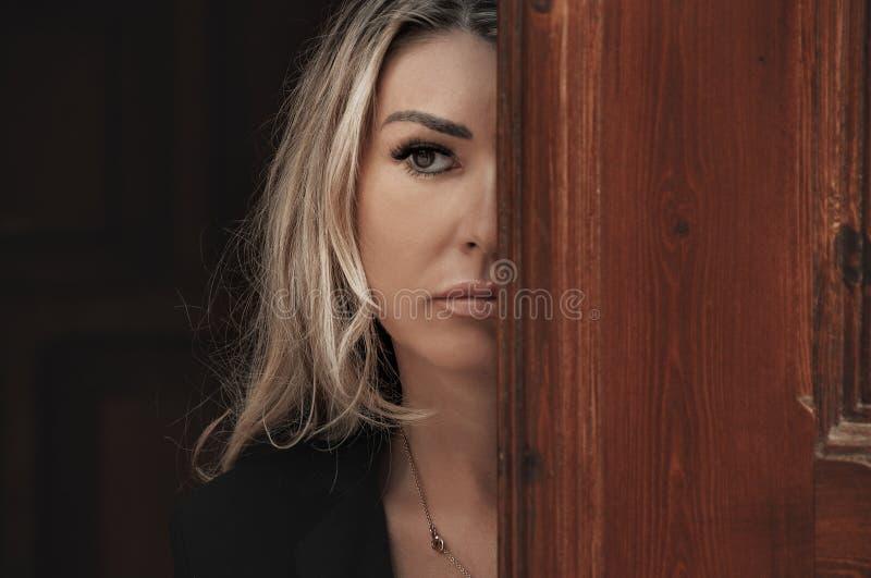 Het mooie meisje gluurt door de deur, glurend uit Deuropening stock foto