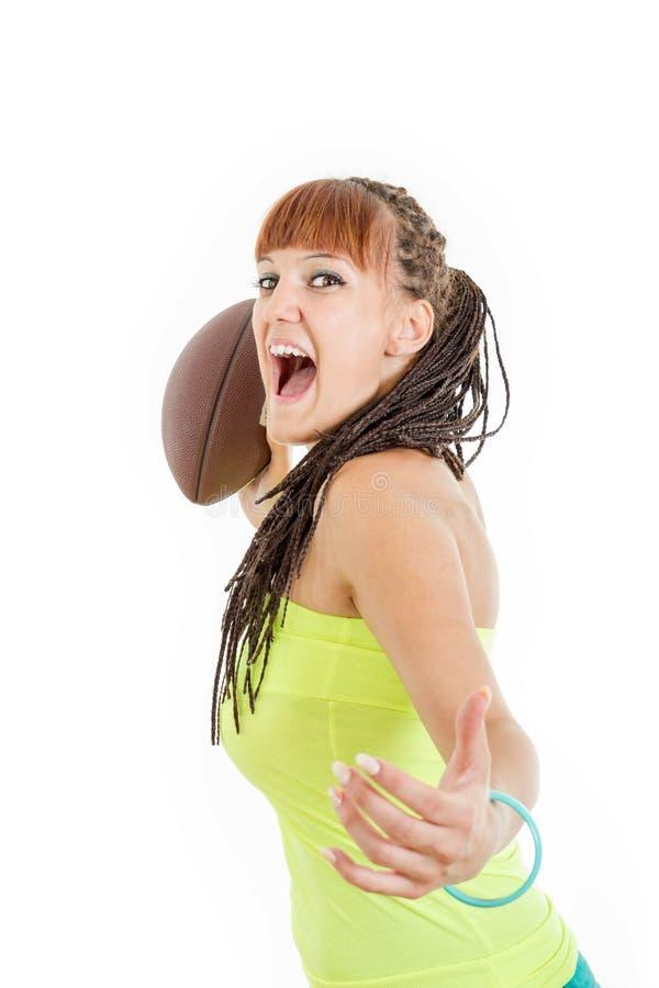 Het mooie meisje in groen overhemd werpt bruine rugbybal naar camer stock afbeeldingen