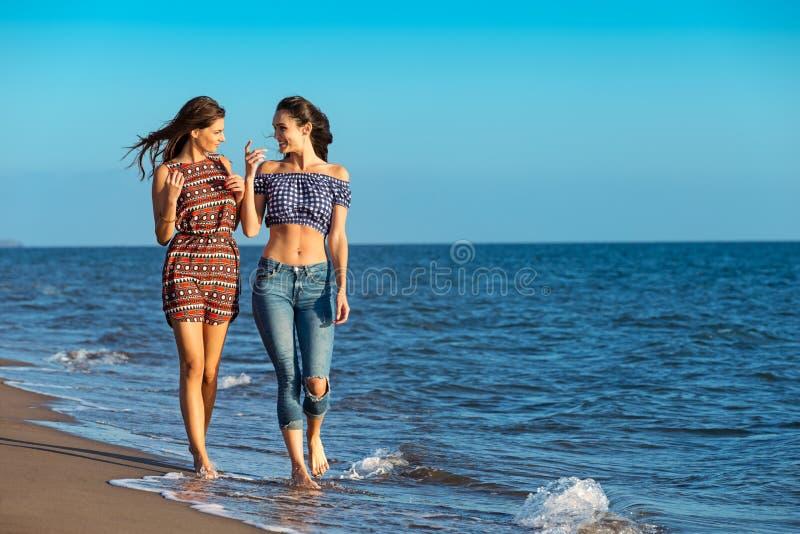 Het mooie meisje heeft een pret met haar meisje op het strand royalty-vrije stock afbeelding